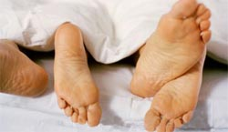 photo of two pairs of feet sticking out of bed
